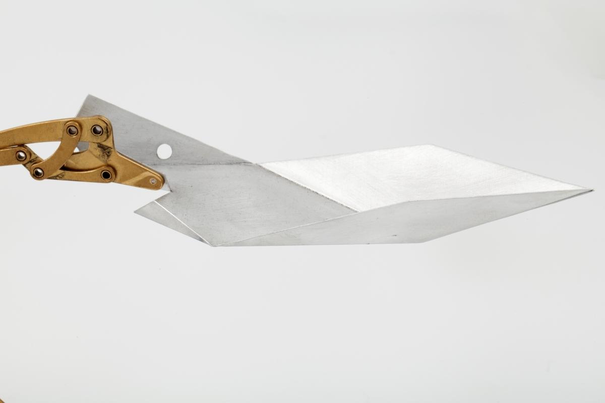 """Kinetisk skulptur i messing og aluminium som folder seg ut. Den kan foldes sammen ved å trykke ned midten av skulpturen. Mekanismen minner om en paraply. Sju armer i messing er sentrert rundt en midtdel som står på fire føtter. Hver arm ender i en spiss brettet """"skuff"""" i aluminium.   Transformer-6.5.01 Pod er fra serien Tribute to the Mars Exploration Rovers."""