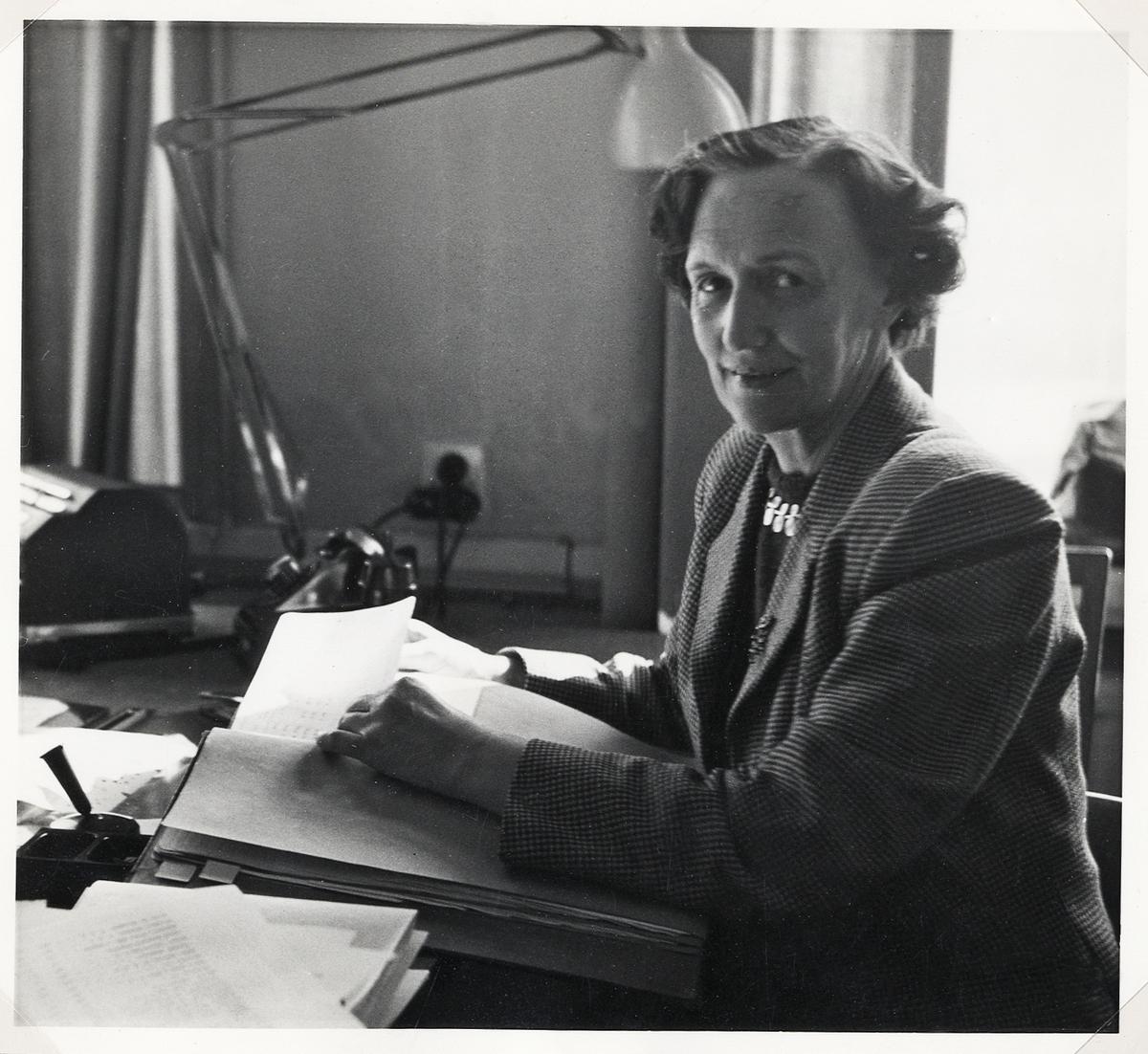 En kvinna i dräkt sitter vid ett skrivbord, ca 1960.  Göta Friman, anställd vid Systembolaget, Växjö.
