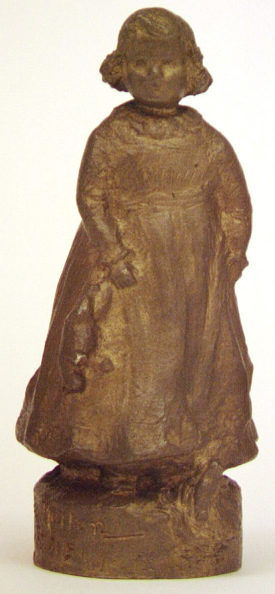 """Skulptur eller statyett av brons, """"En solstråle""""av Ida Matton .Signerad Ida Matton, Paris. Liten flicka med lockigt hår, fotsid klänning med rosett bak. Håller en nallebjörn i höger hand. En docka ligger framför vänstra foten."""