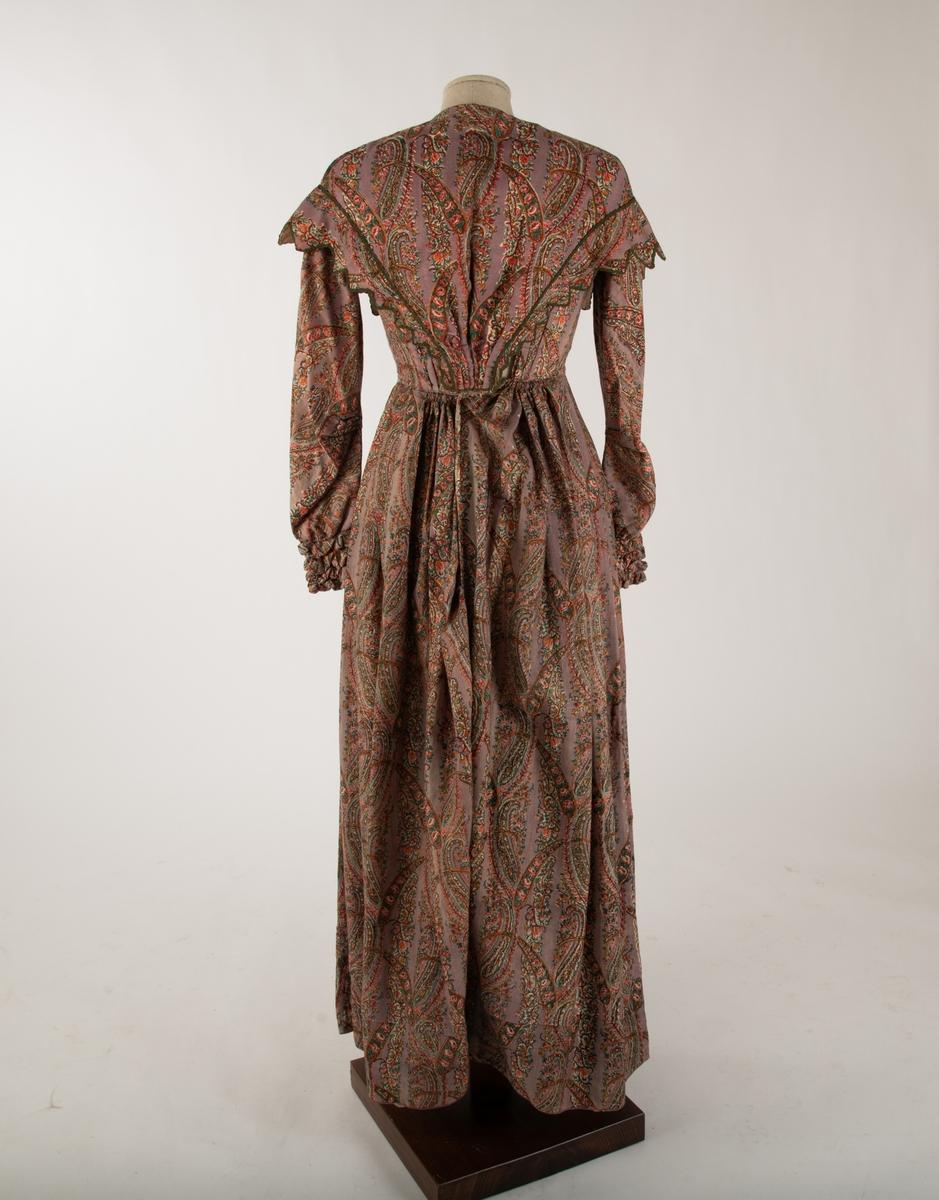 """Kjole i to deler. Kjole med løs krave, en """"Bertha""""-hals/krave. Fotsid kjole med rund hals og lange ermer. Ermene ender i rynkete mansjetter. Mansjettene har hver tre innsydde hemper i metall. Kjolen er i ett stykke, men er laget slik at den ser ut som en underdel og overdel. Forstykket til kjolens overdelen er plissert på midten. og ender i en spiss. Kjolen lukkes bak med 15 hemper i metall.   Kraven har taggete endekant som er linjert med grønt dekorbånd."""
