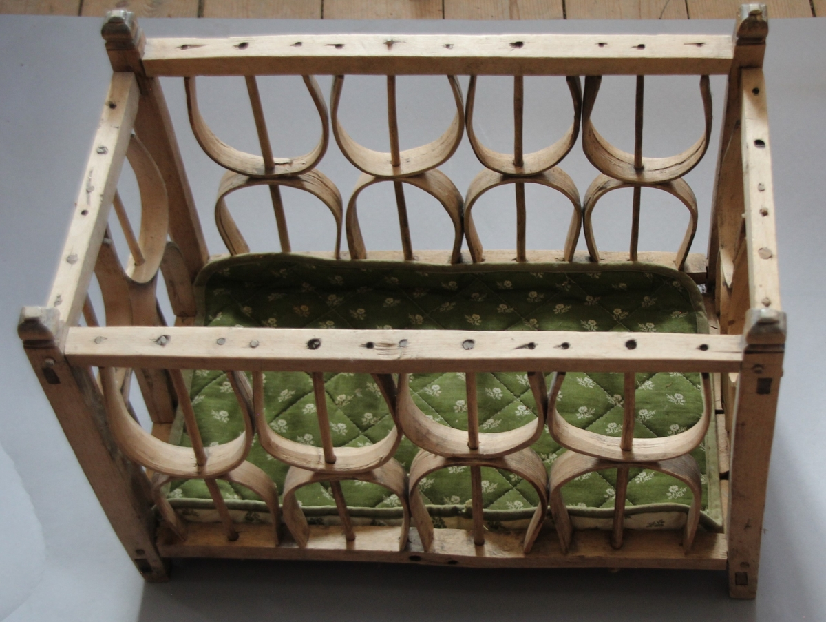 """Rektanguler i form, Sjølve """"grinda"""" er tappa saman og låst med trenaglar. Ein """"stolpe"""" i kvart hjørne. Veggane i """"grinda"""" er laga av spon som er bøygd til halvsirkelformer. Spile i gjennom kvar halvsirkelform. To halvsirkelar oppå kvarandre i høgda.Botn er grov, sett saman av tynne, uhøvla sponbitar. Oppi korva ligg ei tynn, lita madrass i to fargar. Madrassa er trekt med småblomstrete stoff.  Truleg er korva bruka som dokkeseng i seinare tid."""