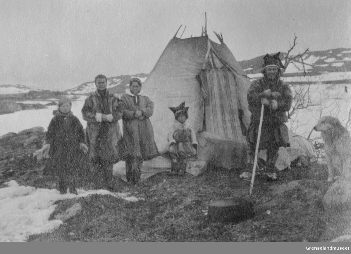 """Samisk leir ved vann """"186"""", Adamselv, 1919. En reindriftsfamilie står utenfor sin lavvo."""