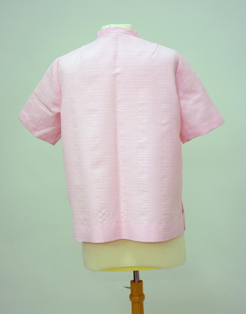 Buksedrakt: Rosa jakke med rett fasong,korte ermer, ståkrave, åpning foran med 4 stk knapper. Hjemmesydd. Tilhørenede bukse i samme stoff. Rette bein, glidelås og knapp foran.