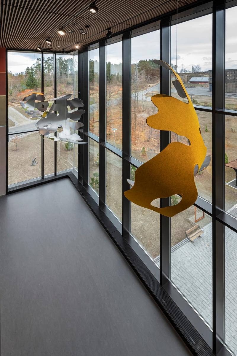 Kunstneren har inntatt rommet med et monumentalt veggmaleri og fire hengende skulpturer. Maleriet er utført på stedet, malt rett på tørr vegg med maling vått i vått og konturlinjer av kritt. Skulpturene er laget av farget ullfilt som er limt på og sydd fast i utskårne og håndbøyde stålplater. Formene er basert på hjerneskanninger fra våre fire største rovdyr: ulv, jerv, bjørn og gaupe. Veggmaleriet kartlegger de forhistoriske vannveienei Ås og omegn.  Tittelen betyr utenfor-sted og refererer til den konserverende prosessen som skal beskytte utrydningstruede arter utenfor deres naturlige habitat. Kunstverket tar for seg tanker om kulturell representasjon, utenforskap og økologisk ubalanse, og danner en forbindelseslinje til Apichaya Wanthiangs maleri i Veterinærbygningen. Der hun viser oss en oversvømmelse i hjemlandet Thailand, har Smebye tegnet opp vannveier fra sine hjemtrakter på Ås.