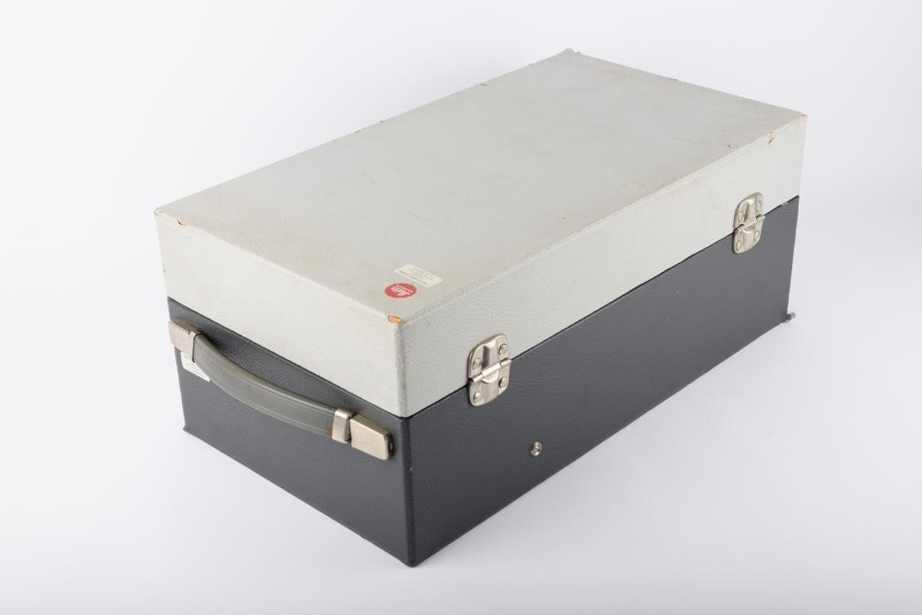 Lysbildefremviser med strømkabel, oppbevart i tilhørende apparatkoffert. En Osram-lyspære i original emballasje ligger også oppbevart i kofferten.  Apparatkofferten har hengslet lokk med to låser i front. Bærehåndtak i den ene kortsiden. Kofferten har noe innvendig polstring for å beskytte projektoren.