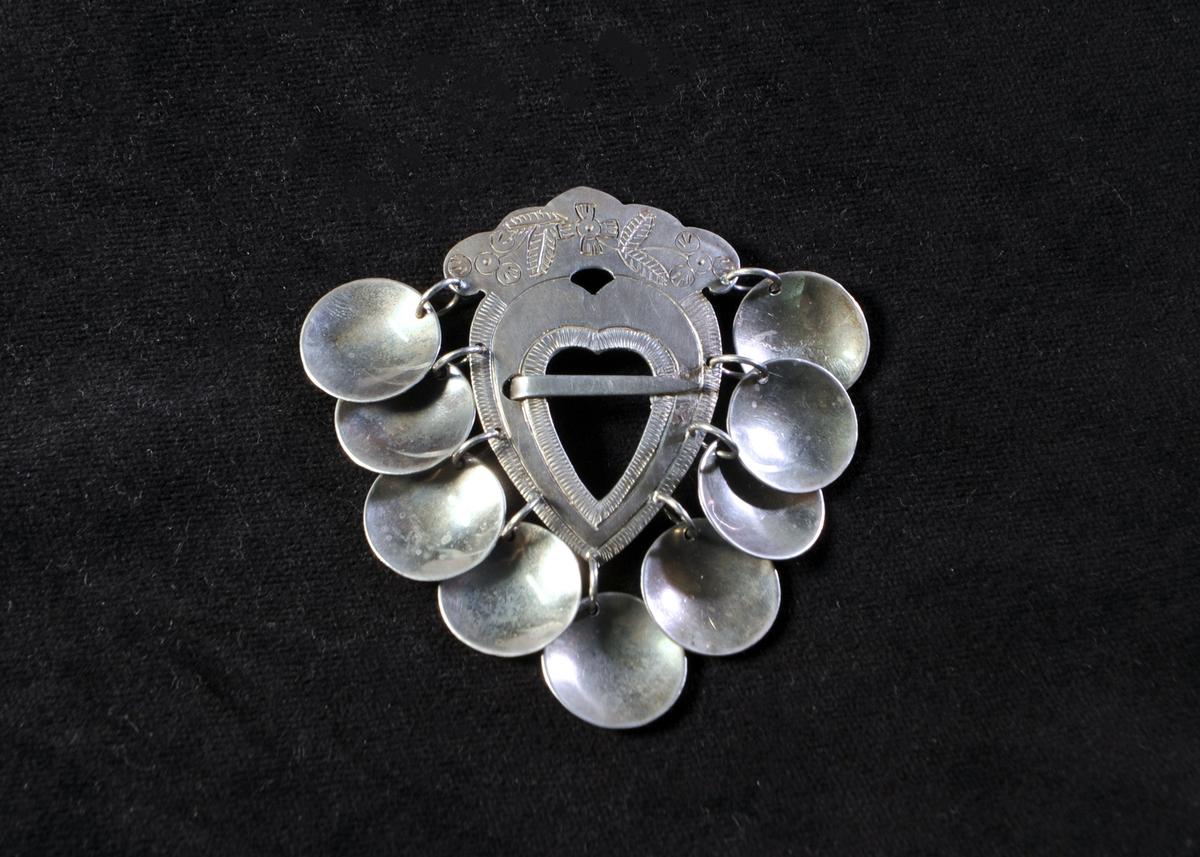 Sölja (bröstsölja eller lövaspänne). Hjärtformat mittstycke som är siselerat. 9 st skålformade hängen. Mitten fastlödd på senare tid och då ersatt med en fästnål på baksidan. Stämplar saknas. Jämför: JM 37 926.