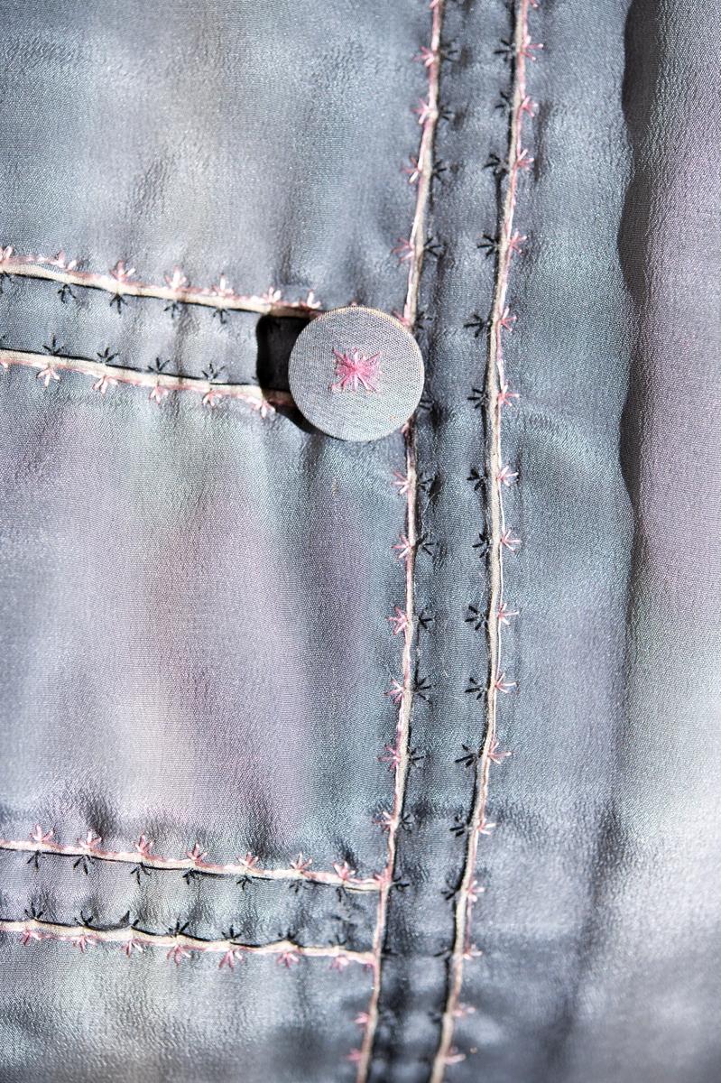 Av blågrått siden. Handbroderad med rosa och svart silke. Handtryckt sidenfoder med blom- och bladmotiv.