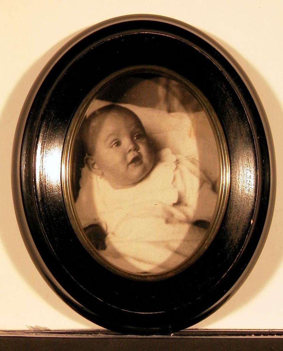 Babyportrett; piken liggende støttet opp av puter.