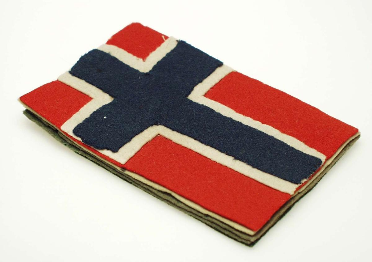 Pennetørker av flere lag filt formet som det norske flagget. Lagene er sydd sammen med fem sting ved flaggkorstet.