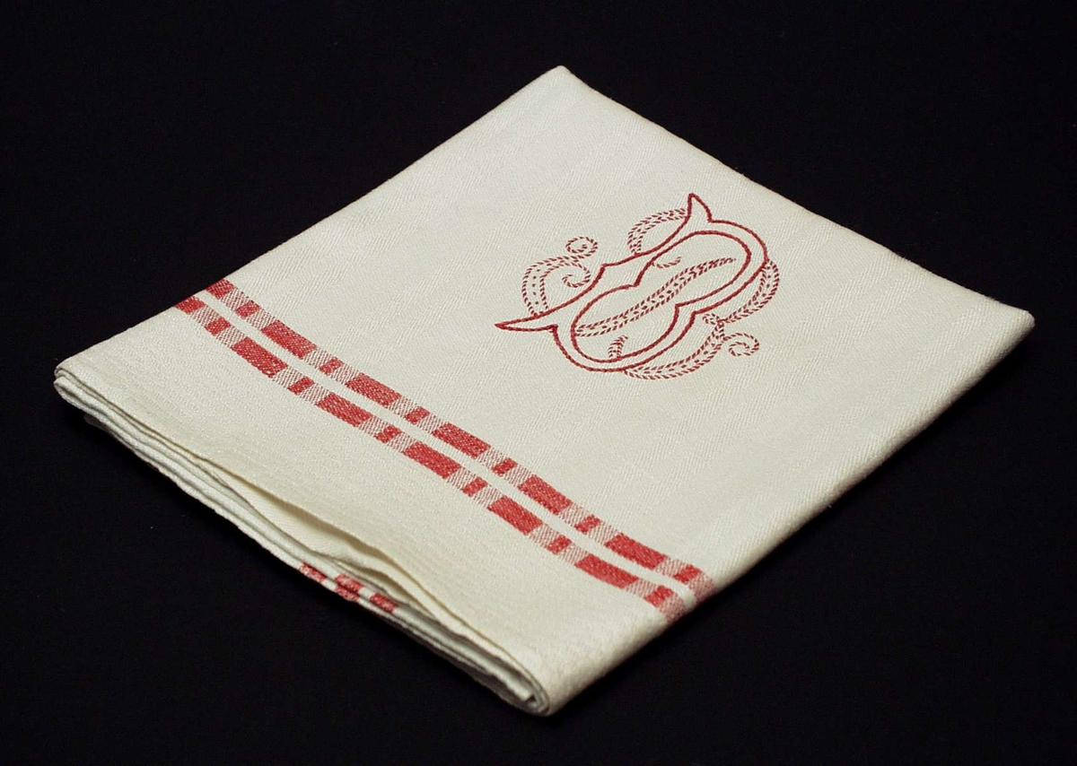 Hvitt linhåndkle med brodert monogram i rødt og hvitt. Vevbredden er 56 cm, jarekant og maskinsydd fald i kortendene. Midtpartiet er langstripet og to rød striper danner bord  6-8 cm fra kantene. Mot ytterkant smalstripete mønstring (hvit) som krysser i hjørnene og danner ruter. Monogram på midten nederst: dobbelt B sydd av rødt og hvitt garn. 1.B av røde kontursting. 2.B av rød leggsøm sydd ned med hvitt garn.