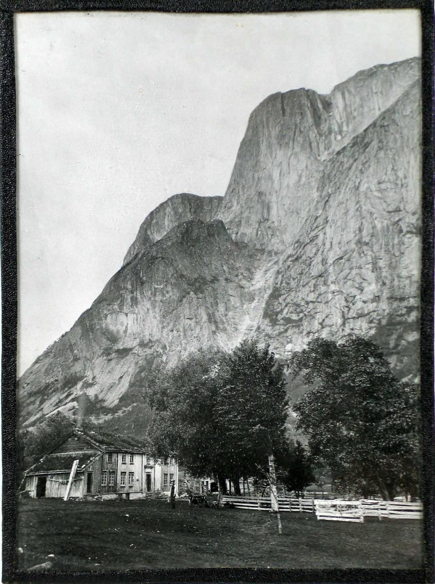 Gård under høye fjell. En mann står foran hovedbygningen.