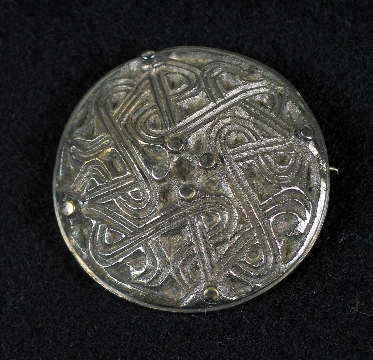 Rund støpt nål i sølv (tinn?) med nordisk mønter.