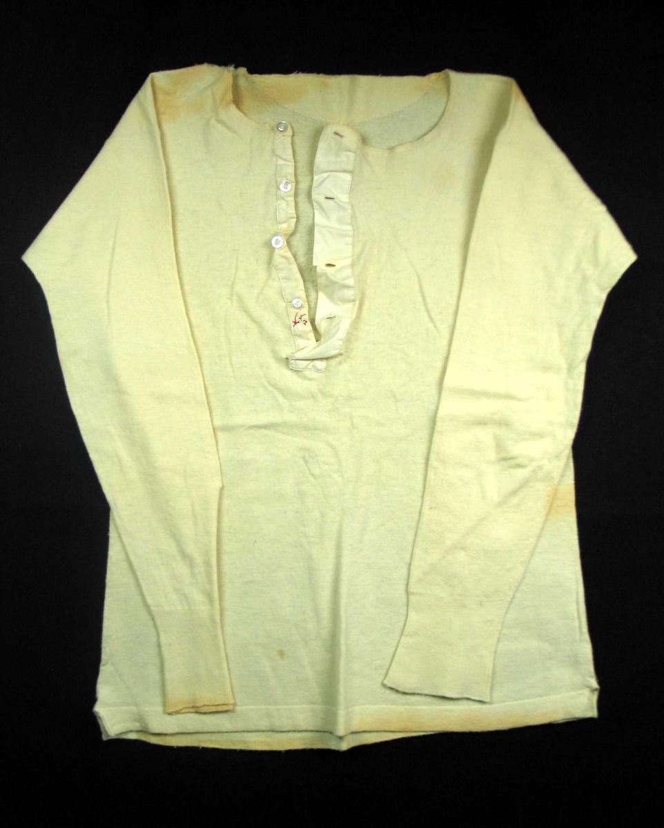 Gulhvit undertrøye i ull og bomull. En høyde, glattstrikket, med bukt over skulder, søm i sidene, splitt med stofforsterkning i samme lengde som nederste oppbrett 2,5 cm. Rundet halsåpning. Rett brettekant i nakke der trøyetøyet fra halshullet er brukt som forsterkning i nakken. Halvmåneformet, 24 cm splitt midt foran, fra halsen og sydd stolpe av lerret. Fire knapper og horisontale knapphull. Herrelukking. Noen sting med rød tråd på undersplitten. Sammensydd skrådd erme med 9,5 cm kvarding. Rett i sydd til bolen.