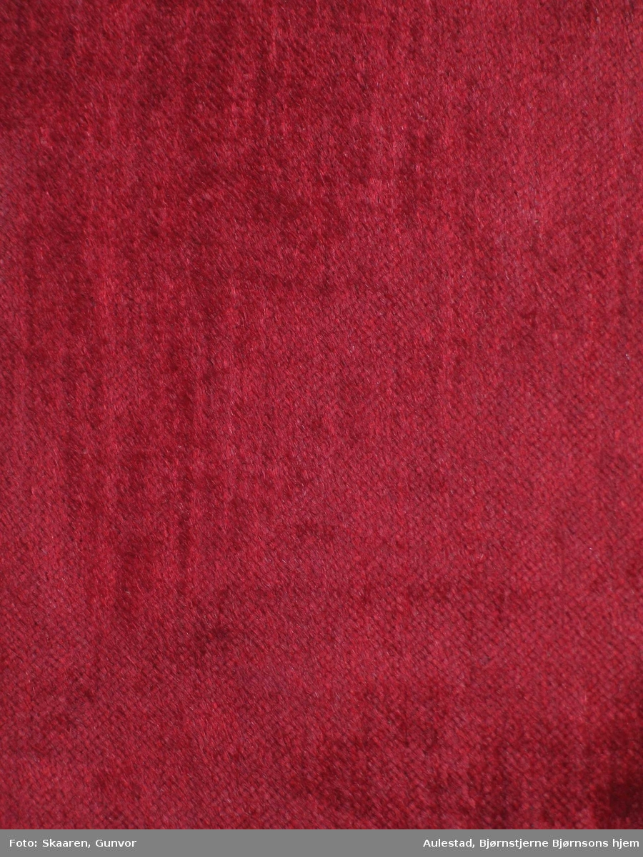Rødt møbelstoff i plysj, ullhår på bomullsbunn.