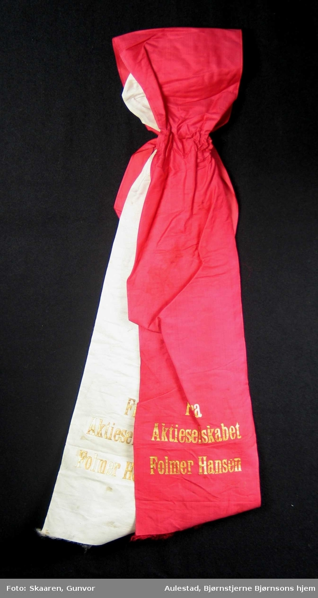 Begravelsessløyfe i hvit og rød silke.
