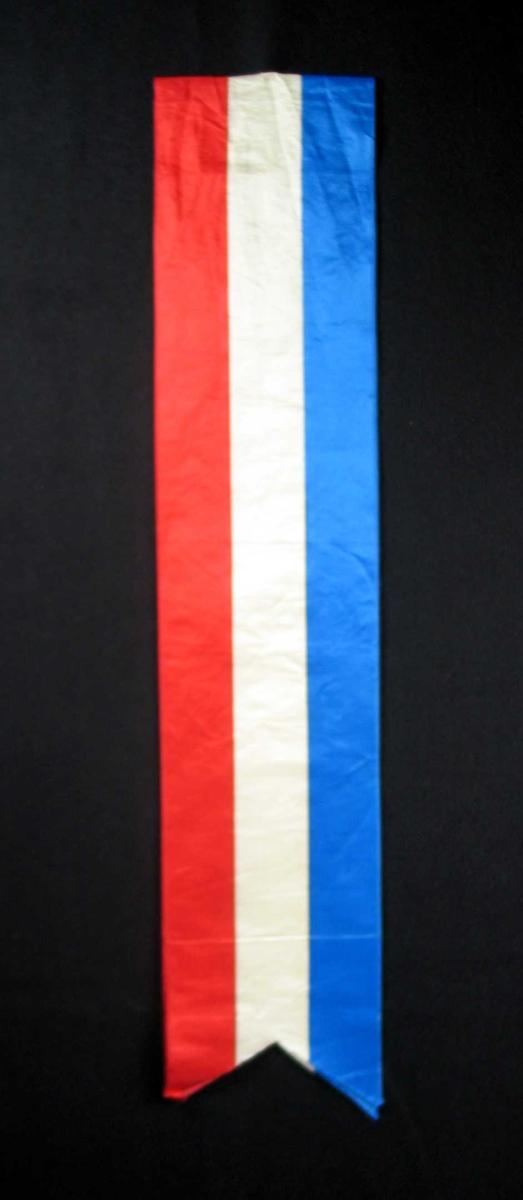 Begravelsessløyfe i hvit, rød og blå silke. Ingen tekst.
