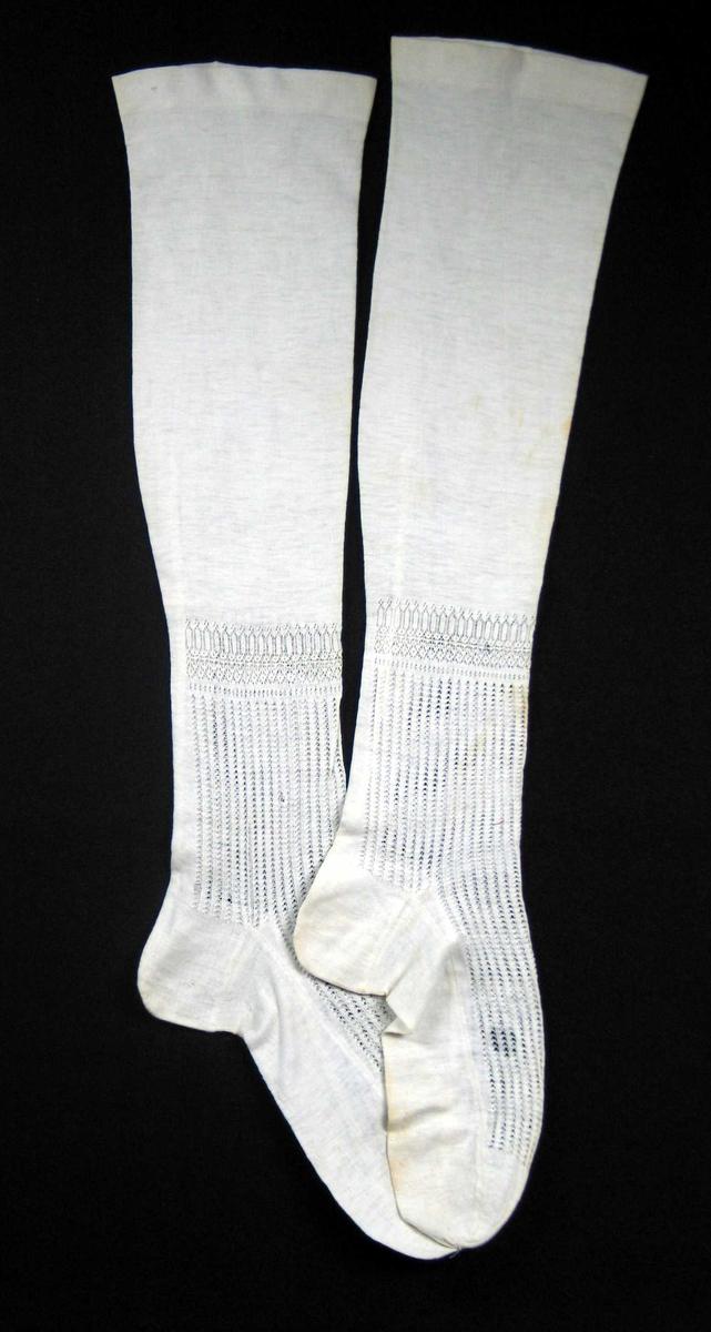 Maskinstrikkede strømper i bomull med gjennombrutt mønster fra 14 cm ovenfor hælen og fram mot tåfellingen. Strømpene har glattstrikket hæl, såle og tå med flat felling.