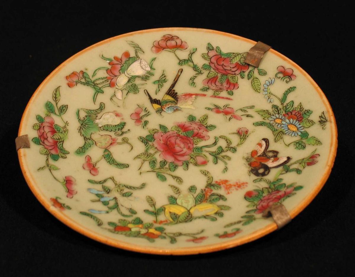Asjett i porselen med lys grønn glasur og polykrom dekor. Motivet er blomster, sommerfugl og fugler. Oppheng på baksiden.