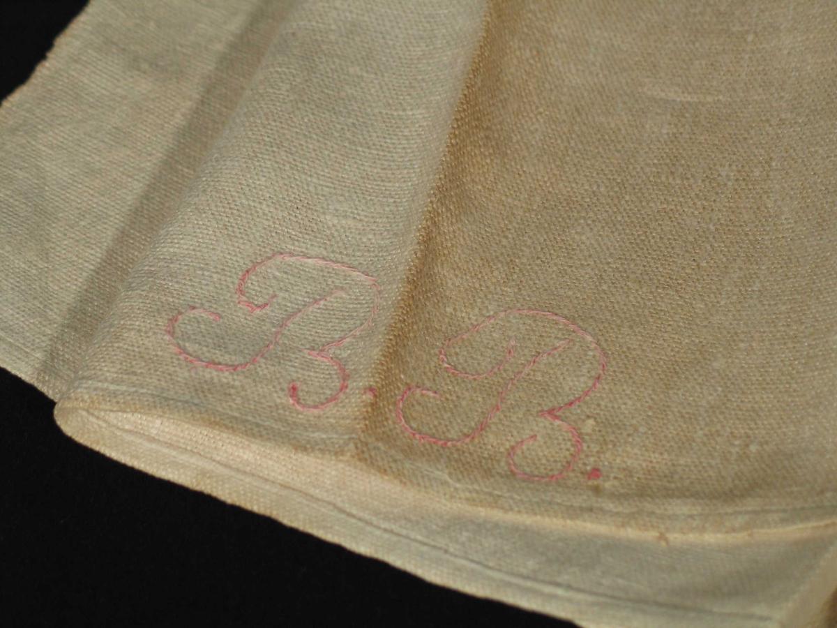 Håndkle i grovlin med brodert monogram i rødt.