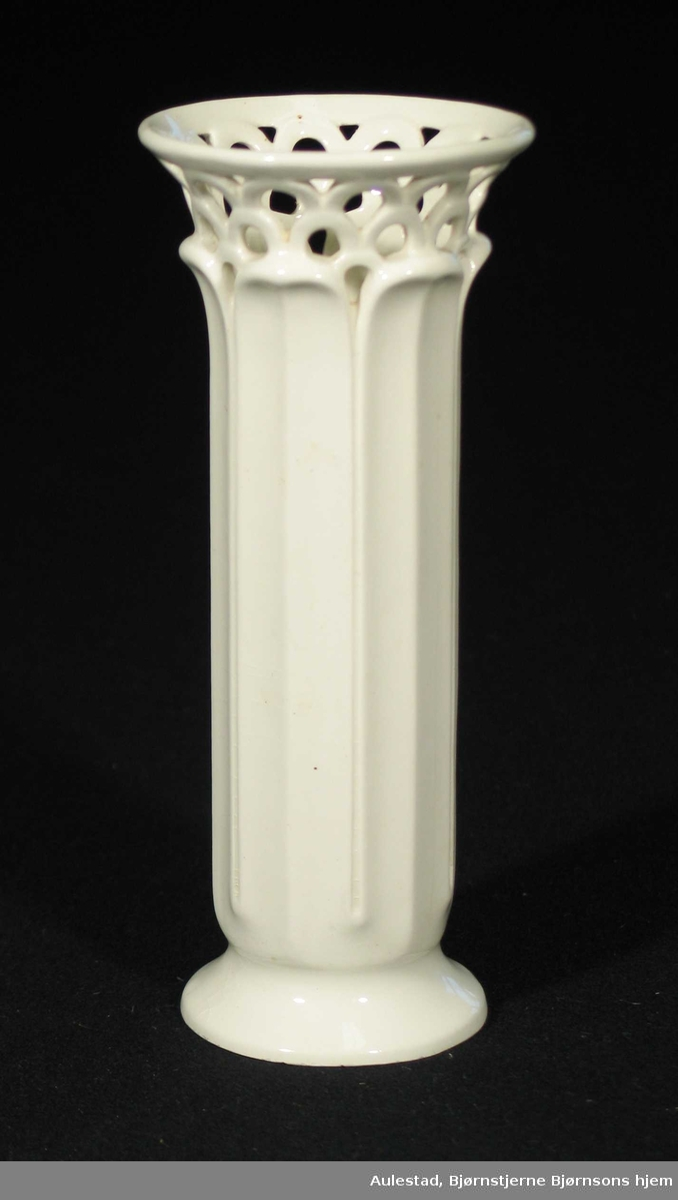 Hvit sylindrisk vase i porselen. Den har utoverbrettet kant øverst med gjennombrutt mønster. Vertikale felt.