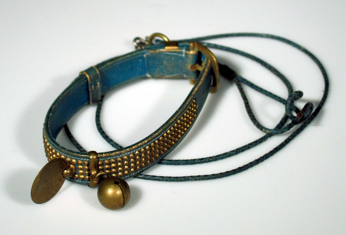 Hundehalsbånd i grønt/blått lær dekorert med nagler i messing. Det har en rund navneplate og rangle festet i ring til båndet. Tvunnet lærsnor.