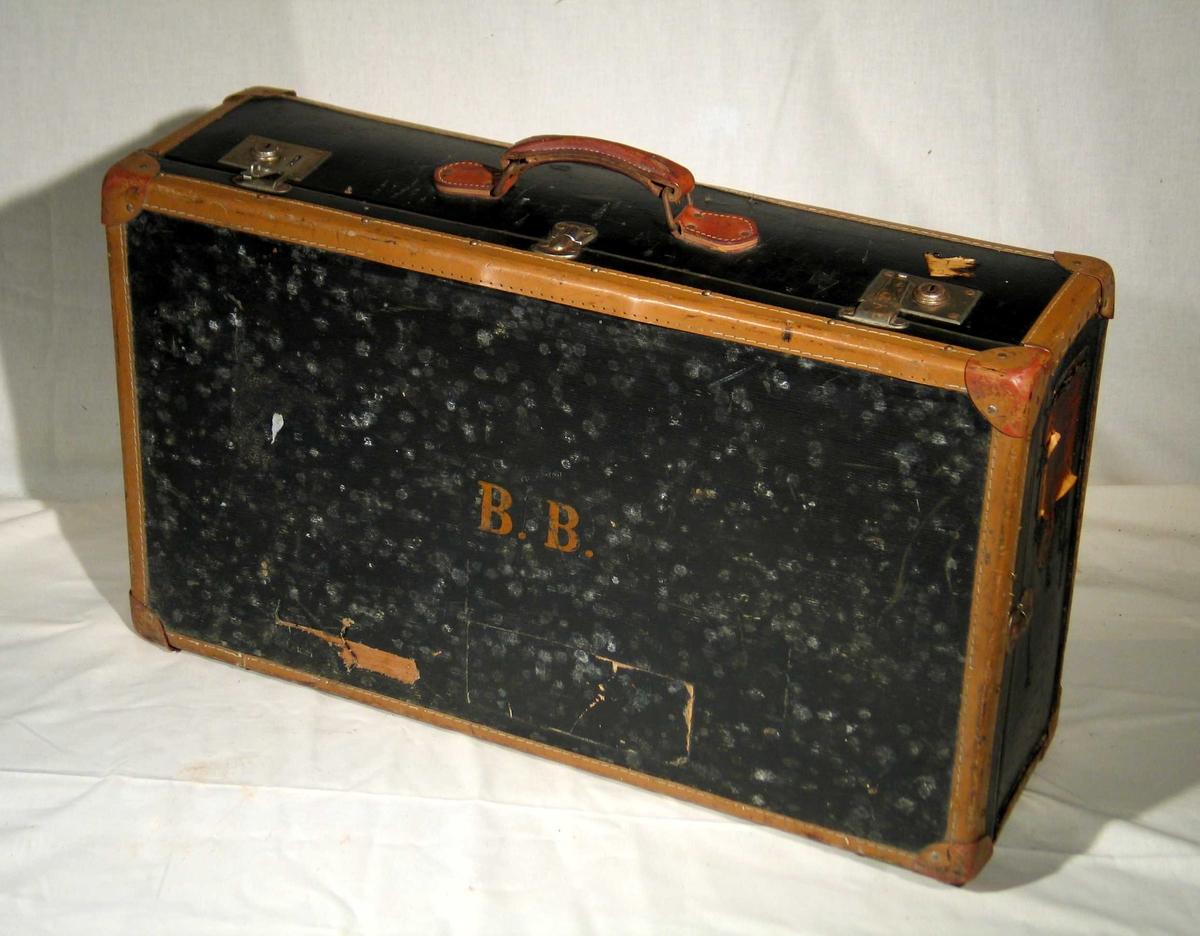 Svart koffert i kartong med brune skinnkanter og metallås. Kofferten er fôret med rutet papir.