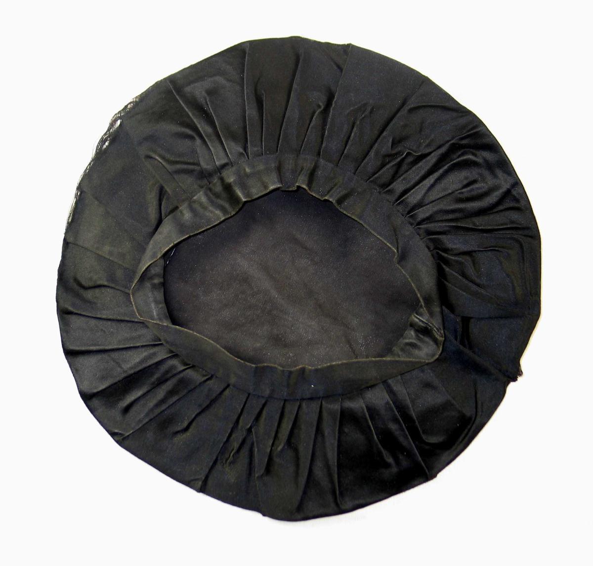 Pull sydd av sirkelrundt stykke silketøy med diam 54 og 46 folder, vendt samme vei, sydd til en tre cm bred og 61 cm lang linning.