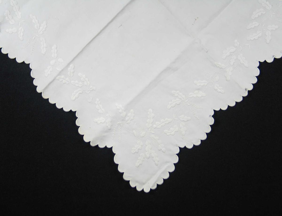 Hvit duk med engelsk broderi i form av eikeblad og eikenøtter i en bord langs ytterkanten. Tungekant. Duken er kvadratisk.