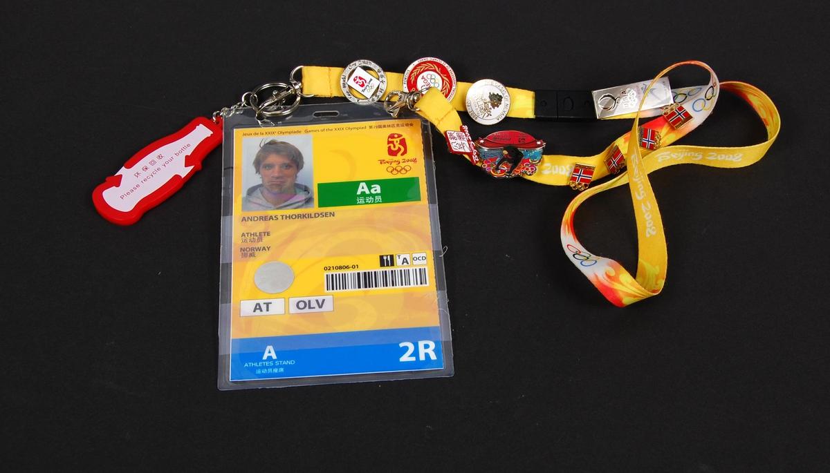 Flerfarget identitetskort med passfoto av Andreas Thorkildsen og logo for de olympiske sommerleker i Beijing i 2008. Til kortet er det festet et bånd med diverse pins laget i forbindelse med OL i Beijing.