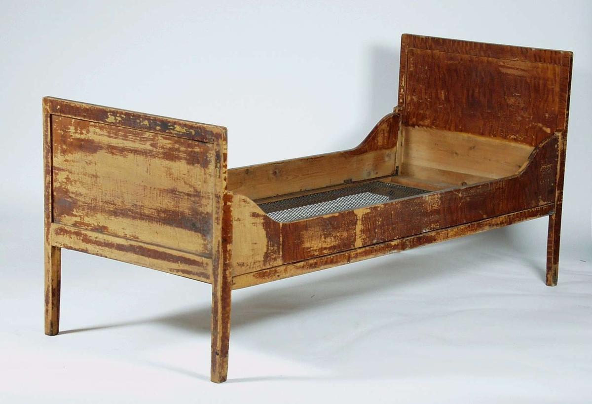 En ådret sammenleggbar seng i furu. Sengen har oppsvingte vanger og gavlene har fyllinger.