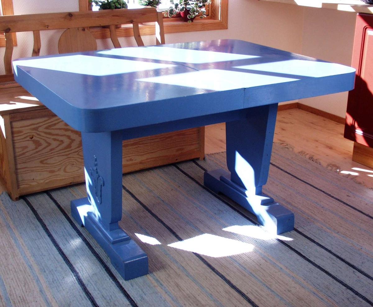 Blåmalt uttrekksbord i tre med utskåret blomsterdekor på sokkelen. Ileggsplatene ligger under bordet.