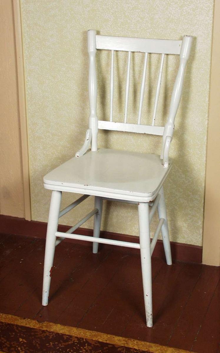 Hvitmalt pinnestol med kantet sete og dreide sprosser. Det er knekter mellom sete og rygg. Stolen er tidligere malt oransje.