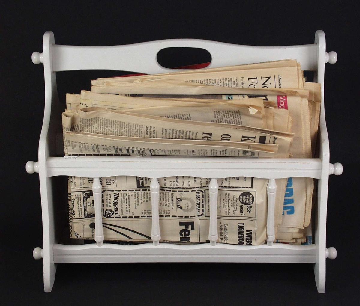 Hvitmalt aviskurv i tre. Den har et håndtak og grinder på sidene.