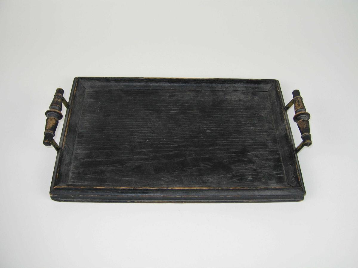 Svartmalt trebrett med treramme. Et håndtak av tre med svartmalte messingstifter på hver ende av brettet.