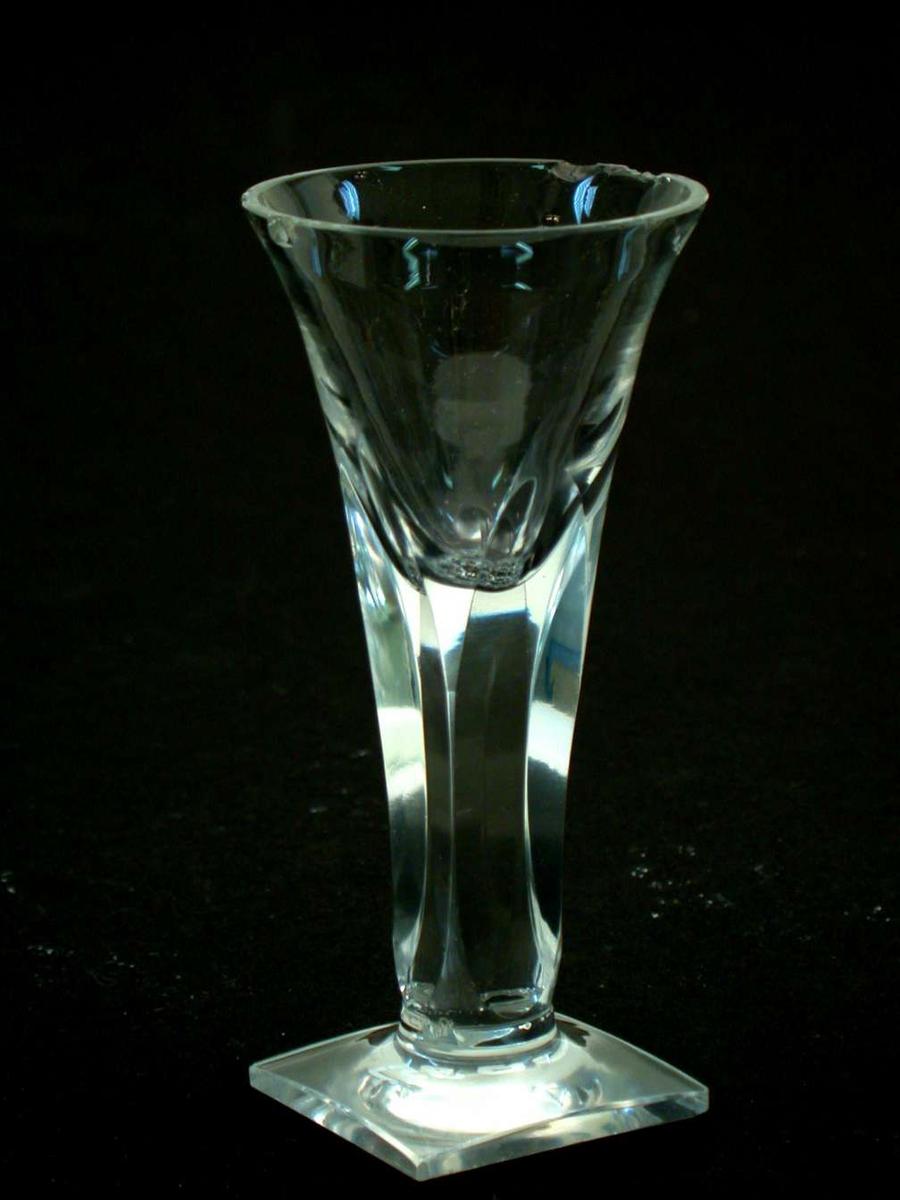 Glasset er et spissglass med firkantet fot. Stetten er fasettslipt slik at den blir firkantet. Det er flere hakk i randen på klokken.