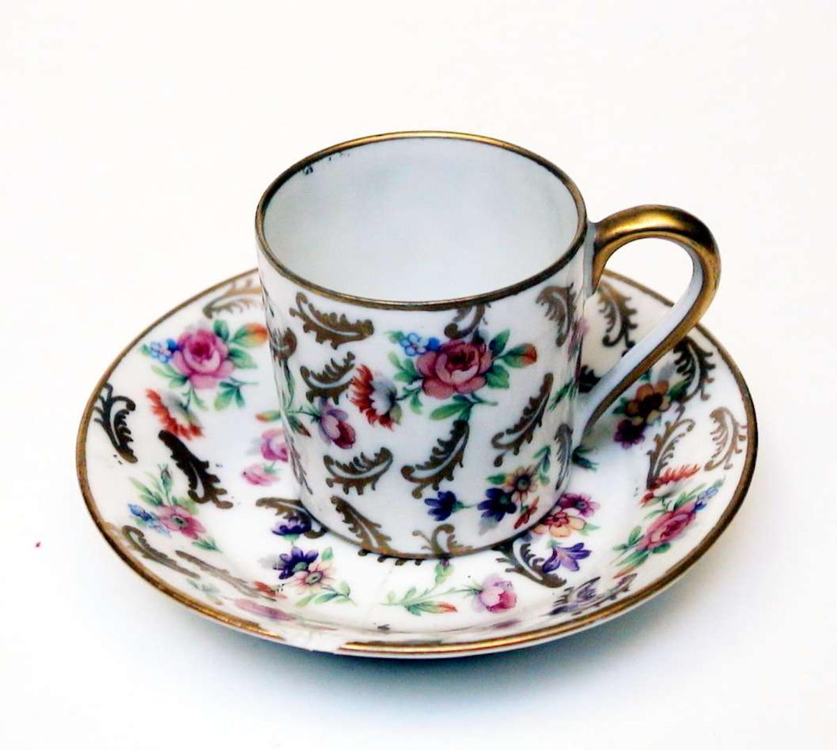 Mokkakopp med skål av hvit porselen. Både kopp og skål er dekorert med blomster og blad i farger og forgylling. Kopp og skål har forgylte kanter. Hanken er forgylt. Skålen er limt og den har et hakk i kanten.