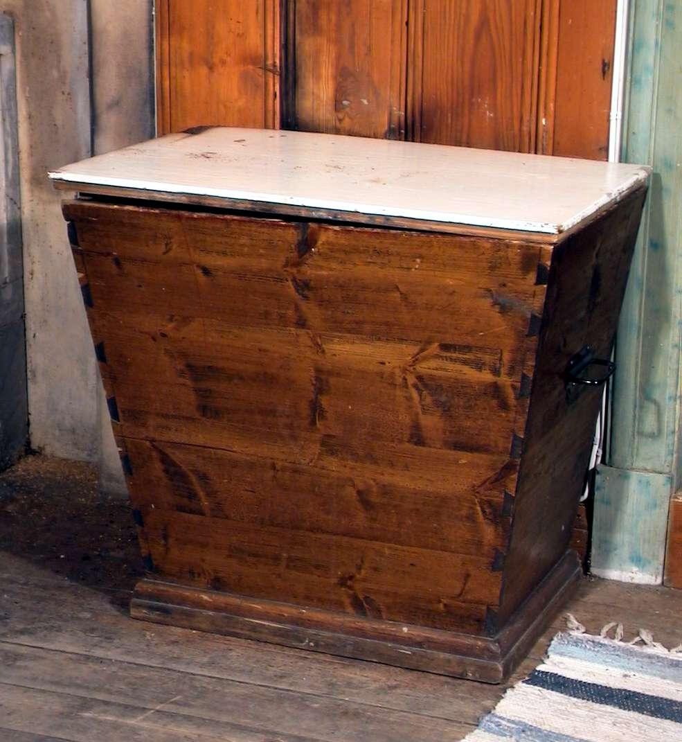 Vedkasse av tre. Kassen er lakkert, lokket er hvitmalt. Vedkassen er brannskadet. Kassen har jernhanker.