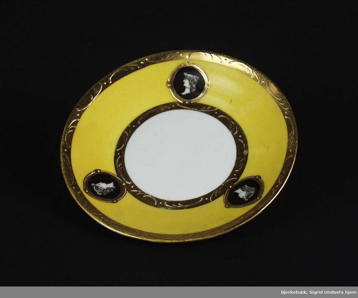 Skål til mokkakopp, gul og hvit med forgylt og sort/hvit dekor. Stempelet er en N med en krone over. Stempelet er orange.