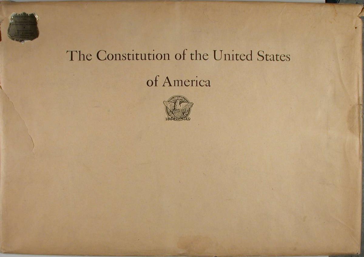 Dobbelt sett med konvolutter som inneholder en faksimileutgave av den amerikanske grunnloven. På den første konvolutten står det skrevet: The Constitution of the United States of America, sammen med et bilde av den amerikanske ørn. Begge konvoluttene har et klebemerke. Faksimilen er trykket og utgitt av Norman T. Munder, Baltimore. (Copyright 1935 Norman T. A. Munder, Baltimore, Md.)