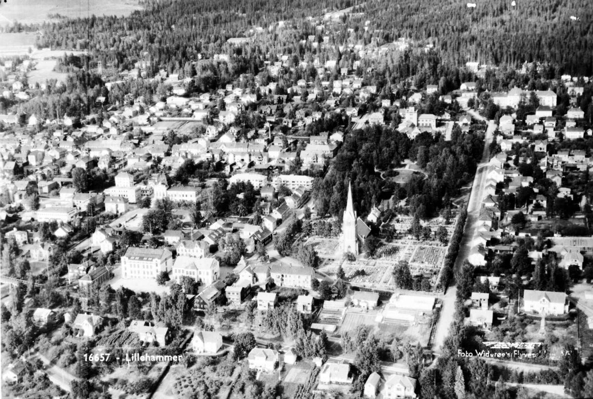 Flyfoto, Lillehammer sentrum sør, med Lillehammer folkeskole (Hammartun) til venstre, og kirken, Søndre park og Mathiesens gate mot sykehuset til høyre. Mot Lillehammer turisthotell og del av Lysgårdsjordet bak til venstre.