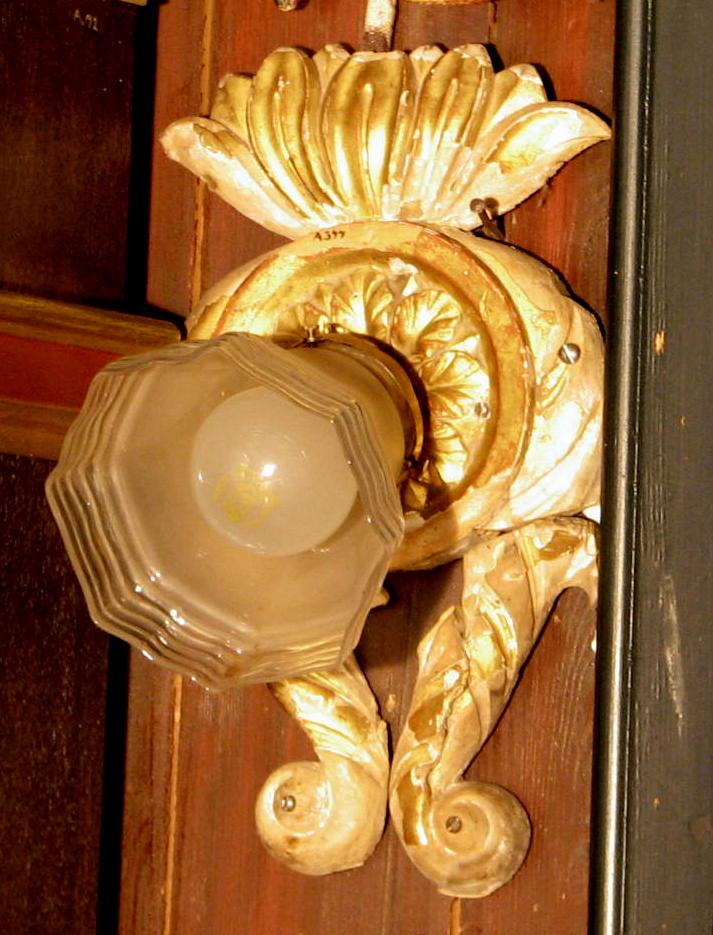 Sirkelformet feste m. rosett kront av bladkalle, volutter under og lampeholder, skjerm av glass.