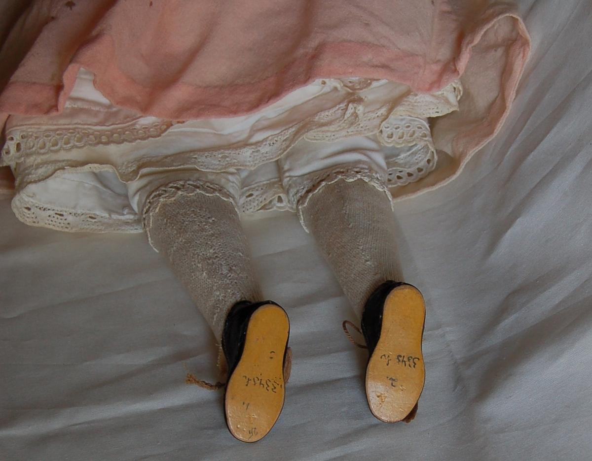 Hode og armer er av stentøy.  Lyserød kjole pyntet med hvite blonder og lyserøde silkesløyfer.   Linnet, bukse, 2 underskjørt med blonder,  hvite bomullsstrømper,  sorte sko med brunt stoff og brune lisser.
