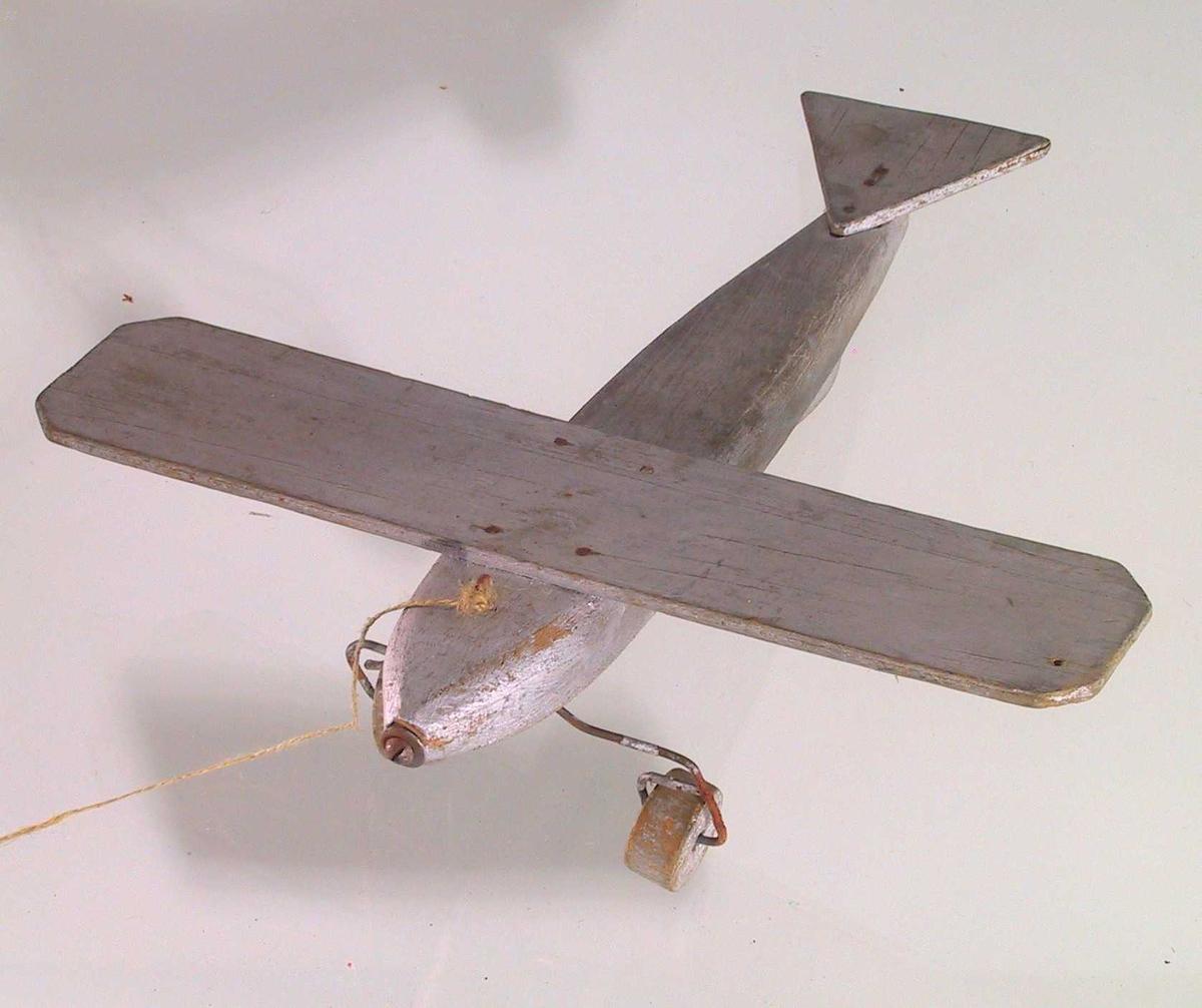 Form: Avlang flykropp, tilspisset i endene og med avrundete kanter. Flatt, avlangt trestykke spikret fast på oversiden som vinger. Liten, trekantet plate spikret fast bakerst. Skrue foran, propell mangler. To landingshjul fetstet med ståltråd på undersiden.