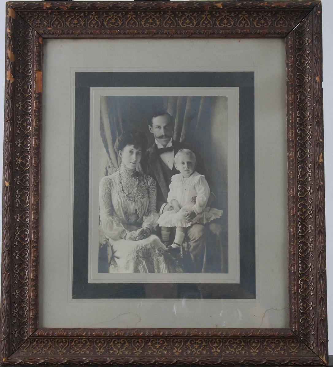 Kongefamilien. Dronning Maud, Kong Håkon VII og kronprins 0lav.  Maud sittende tv.  th. for henne med kronprinsen i hvite klær på  fanget.   Svakt brun toning. Usignert. På lys grå kartong med mørkere grå kant.
