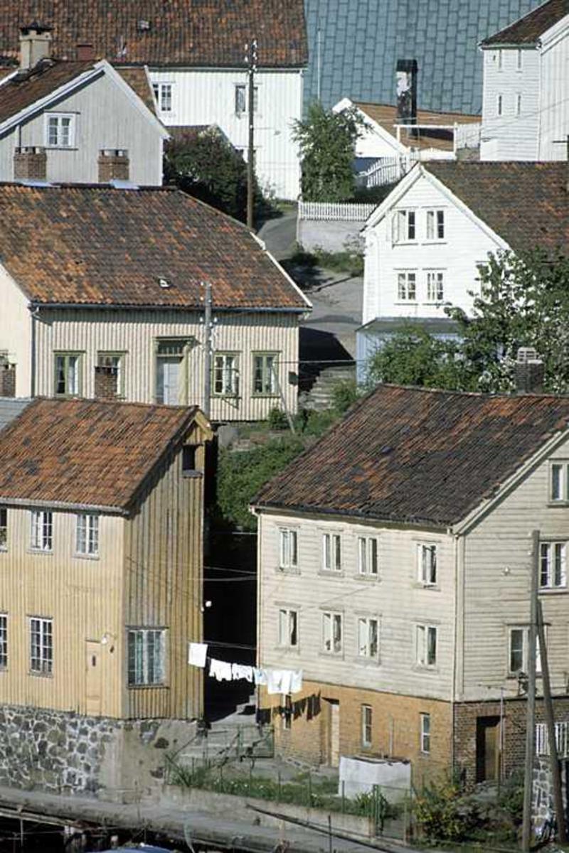 Bebyggelse på Øvre Tyholmen med kirketaket i bakgrunnen. Sett fra Vesterveien. Klesvask på snor. Før restaurering av husene.