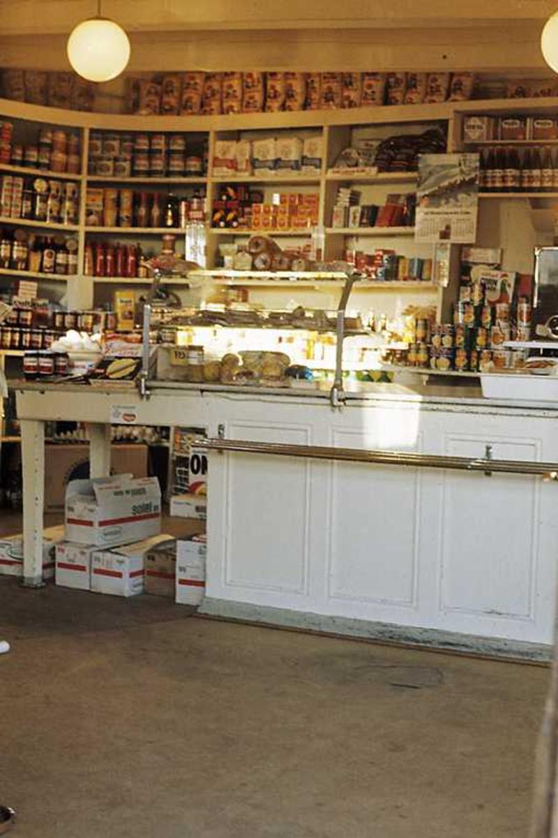 Tyholmen. Det gamle politikammer. Interiør. Dagligvarebutikk. Disk, hyller med varer på veggen, runde lyskupler fra  taket.