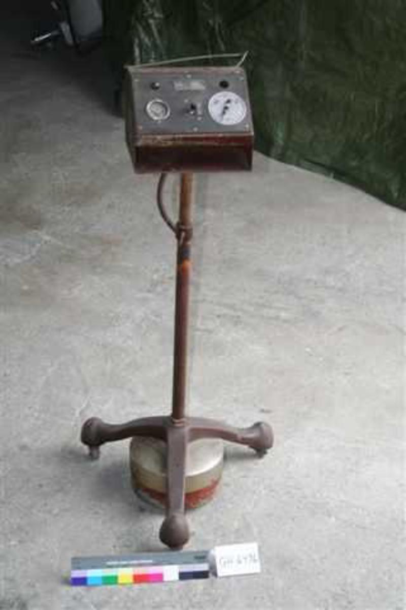 Form: Stang med tre føtter m. hjul. Øverst en liten kasse med skuff til permanentspoler. Skråplan med voltmeter og diverse knapper/innstillinger.