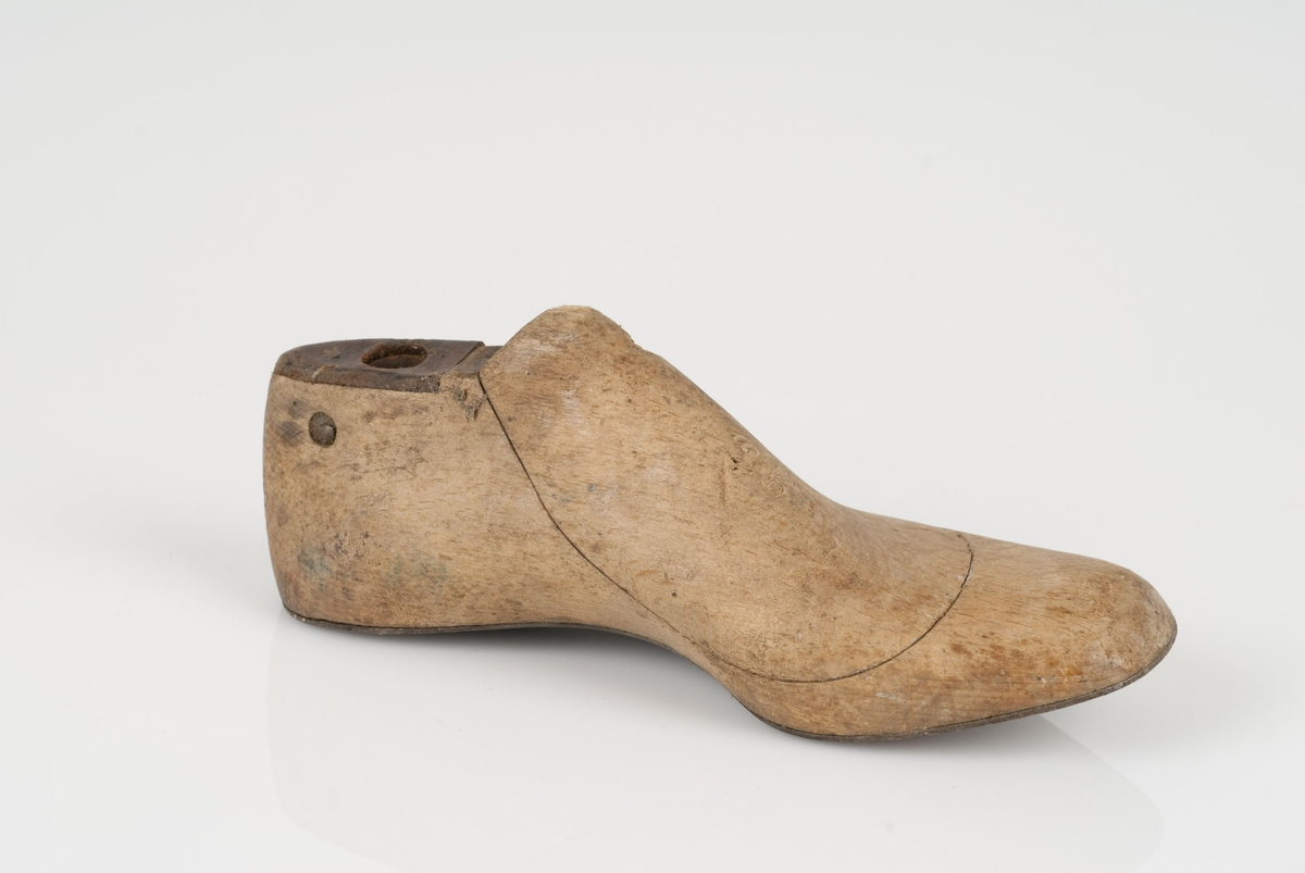 En tremodell i to deler; lest og opplest/overlest (kile). Venstrefot i skostørrelse 29 med 8 cm i vidde. Såle av metall. Lestekam av skinn.