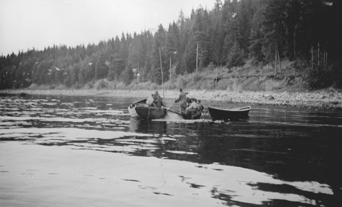 Fra et fiskevær. flere menn fisker med garn fra båt.