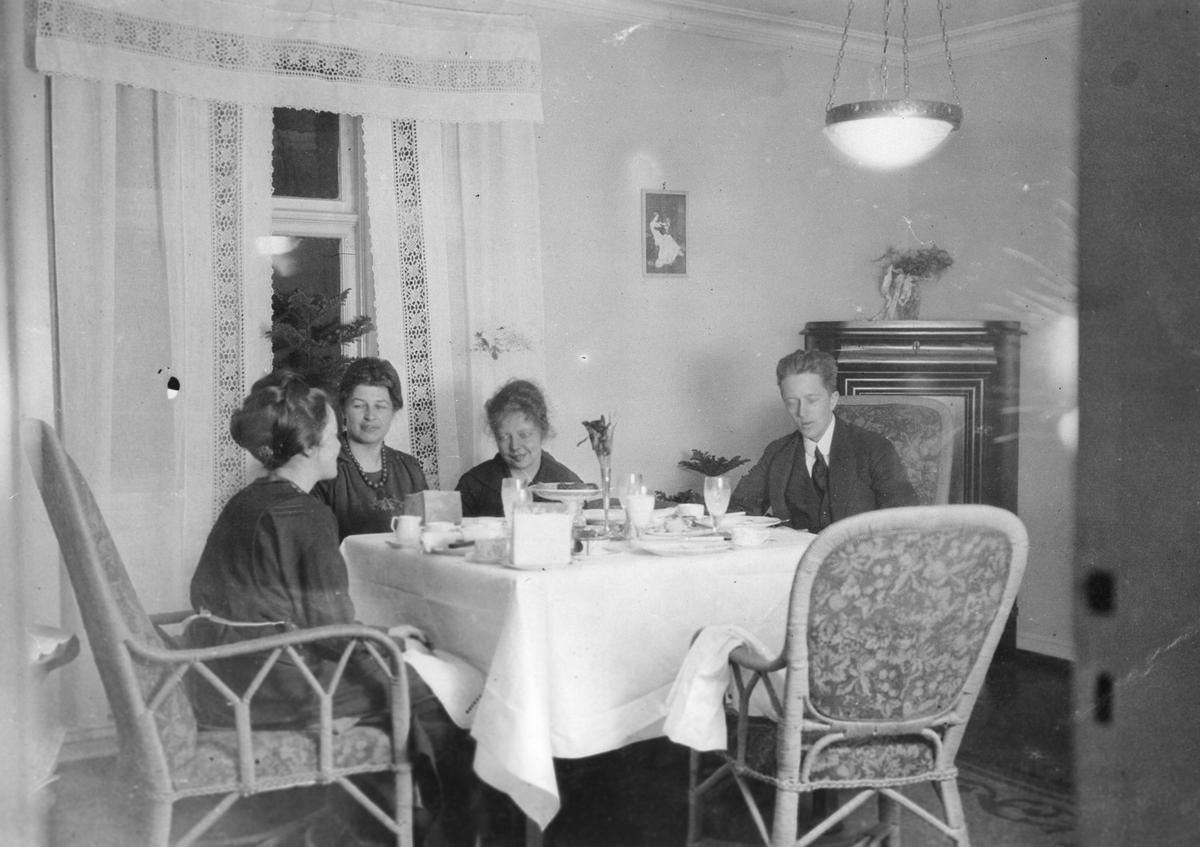 Tre kvinner, en mann, oppdekket bord, hjørneskap, interiør stue